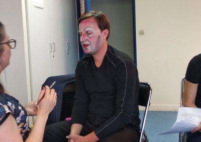 Un comédien de théâtre se fait maquiller.