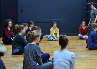 Des adolescents font des exercices de théâtre.