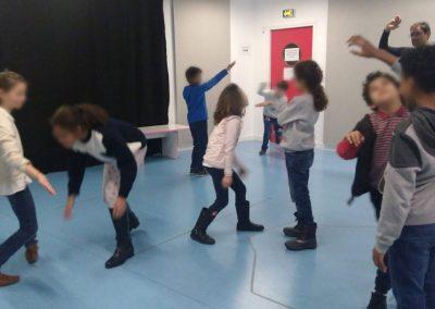 Des enfants de primaire réalisent différents exercices de théâtre.